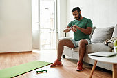 Start. Full length shot of young active man checking time in smartwatch during break, doing morning workout with dumbbells on yoga mat at home. Fitness, motivation concept