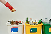 Hand in red glove throwing paper into one of three colorful green, yellow and white recycle garbage bins full of rubbish isolated on white background. Waste separation concept