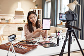 Everything you need. Beauty blogger woman filming, advertising app on camera, holding tablet pc. Makeup influencer asian girl recording cosmetics product review at home