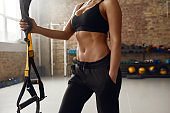 In Love with Exercise. Cropped shot of sportive woman holding fitness straps while having workout at industrial gym