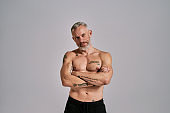 Be an inspiration. Half naked middle aged muscular man looking at camera, showing his body, while posing in studio over grey background