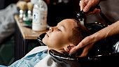 Haircut for kids. Close up photo of a male barber washing hair of cute little boy in barbershop. Kids in barbershop
