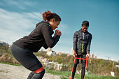 Young athletic african fitness couple in sportswear exercising together in the park, using resistance band outdoors against blurred city background