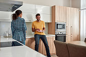 We love our home. Happy multicultural couple in casual clothes wiping the dishes and talking with each other while standing in their modern kitchen. Cleaning home