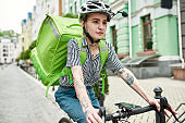Young delivery woman in helmet with thermo bag or backpack riding a bike along the city, delivering food. Courier, delivery service concept