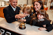 Fully enjoy your stay. Happy family checking in hotel at reception desk. A son and a daughter are ringing a service bell together with parents while standing at the hotel reception.