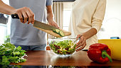 Cropped shot of man putting sliced cucumber in a dish while woman helping him, holding the salad dish. Vegetarians preparing healthy meal in the kitchen together