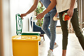 Be clean, be green. Young couple in casual clothes sorting garbage while cleaning their kitchen together. Cleaning home, recycling, housework, family life concept
