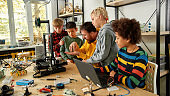 Productivity is the best for us. Group of smart kids listening to their male teacher while looking at 3d printer and plastic detail prototype at robotics school lesson