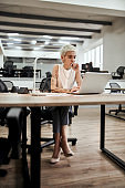 Young focused tattooed female designer using laptop while working at her desk in the modern office. Focus on a girl