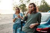 Young couple, man and woman drinking hot coffee or tea after repairing the car during their road trip