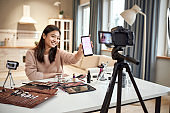 Spread your charm. Beauty blogger woman filming, advertising app on camera, holding smartphone. Makeup influencer asian girl recording cosmetics product review at home