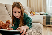 A small cute girl lying on her stomach on a sofa scrolling her tablet