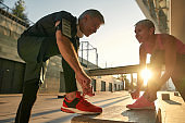 Working out together. Fit and healthy senior couple in sports clothing tying shoelaces before jogging outdoors