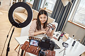 Moving forward digitally. Asian female blogger showing cosmetic products while recording a tutorial video for her beauty blog using camera at home