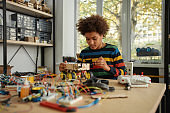 Do the right thing. Boy using screwdriver while fixing bolts on a robot vehicle. Smart kids and STEM education.