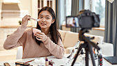Be simply beautiful. Female beauty blogger filming, advertising homemade cream on camera, holding it. Young influencer recording product review at home