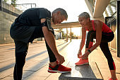 Healthy family. Active middle-aged couple in sports clothing tying shoelaces before jogging outdoors. Exercising together