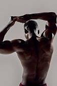 Close up of back of a young muscular african american bodybuilder raising his arms while posing shirtless isolated over grey background. Sports, workout, bodybuilding concept