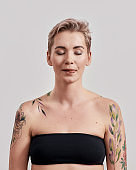 Portrait of a young half naked tattooed woman with closed eyes licking lips with tongue isolated over light background