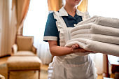 Service truly different. Cropped shot of hotel maid in uniform holding stack of clean white towels for guests while cleaning and preparing the room