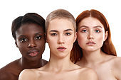 Different types of skin. Portrait of three beautiful multicultural young women embracing and looking at camera while standing close to each other in studio against white background