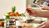 Close up of process of cooking. Man preparing meal while woman checking recipe using tablet. Vegetarians cooking in the kitchen together. Vegetarianism, healthy food, diet, stay home concept