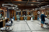 Barbershop interior. Young barber making haircut, serving client in the modern barbershop. Hair salon