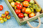 Set of ripe tomatoes in the wooden tray, wooden background