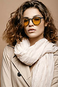 beauty fashion model with clean skin and curly hair in biege cloak stretch with scarf on biege background, model in fashion glasses
