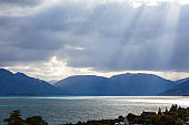 Beautiful landscape with high rocks with illuminated peaks, stones in mountain lake, reflection, blue sky and yellow sunlight in sunrise. Wanaka. Tekapo.