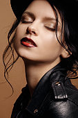 young beauty fashion model woman in  hat portrait on a beige background, black leather jacket, red lips, skin care