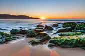 Sunrise by the Sea and Rocks on the Shoreline