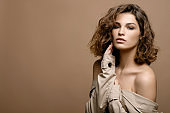 beauty fashion model with clean skin and curly hair in biege cloak stretch with scarf on biege background, copy space, bare shoulders