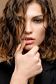 closeup portrait of beauty fashion model with clean skin and curly hair in black jacket on biege background, hands near lips