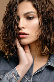closeup portrait of beauty fashion model with clean skin and curly hair in jeans denim jacket on biege background, wet hair of model