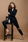 beauty fashion model with clean skin and curly hair in black jacket on biege background on the chair, serious business woman