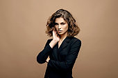 beauty fashion model with clean skin and curly hair in black jacket on biege background, serious business woman