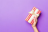 Flat lay of woman hands holding gift wrapped and decorated with bow on purple background with copy space. Christmas and holiday concept