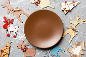 Top view of empty plate and New Year decorations on cement background. New year serving for festive dinner. Reindeer and Christmas tree. Holiday family dinner concept