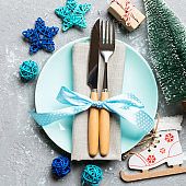 Holiday composition of Christmas dinner on cement background. Top view of plate, utensil and festive decorations. New Year Advent concept with copy space