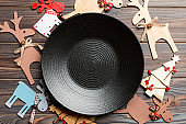 Top view of empty plate and New Year decorations on wooden background. New year serving for festive dinner. Reindeer and Christmas tree. Holiday family dinner concept