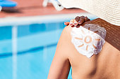 Gorgeous woman has a sun shaped sunblock on her shoulder by the pool. Sun Protection Factor in vacation, concept