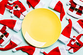Festive set of plate decorated with Santa Claus hat on colorful background. Top view christmas dinner concept