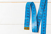 Top view of measuring tape on wooden background. Tailor and slim waist concept with emty space for your idea