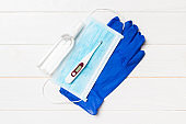 Top view of latex gloves, bottle of alcohol hand sanitizes, medical mask and digital thermometer on wooden background. Antibacterial virus protection concept with copy space