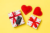 Top view of car key on gift box and red textile hearts on colorful background. Present for Valentine's Day concept