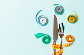 Diet concept with fork and knife surrounded with colored measuring tapes on blue background. Top view of weight loss with empty space