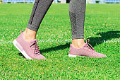 Crop image of female sporty legs and feet in running shoes at the stadium