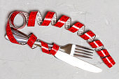 Diet concept with fork, knife and measuring tape on gray background. Top view of weight loss